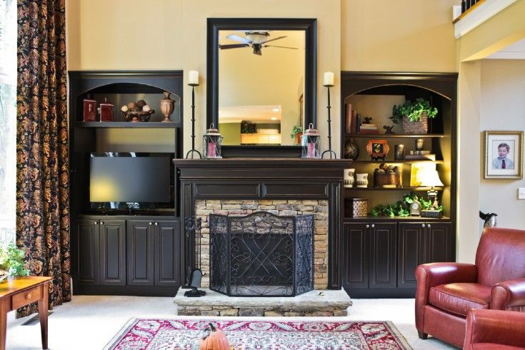 Black built in cabinet by black fireplace mantle in family room ...