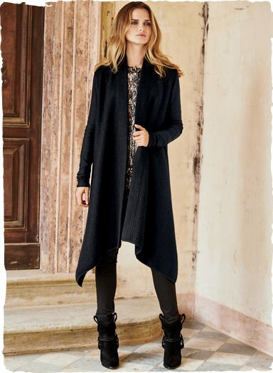 Minimalism at its best, the knit coat is softly felted black baby alpaca (79%), modal (16%) and nylon (5%), with slim-fitting knit sleeves, a drapy open placket and floaty, asymmetrical hem.
