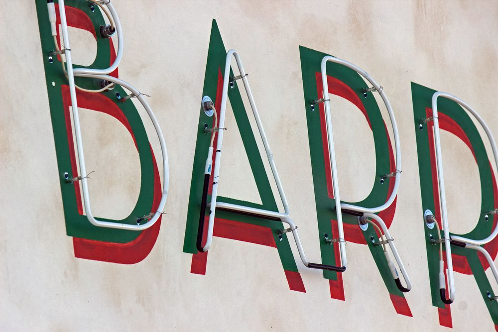 An up close shot of the painted and neon wall sign.
