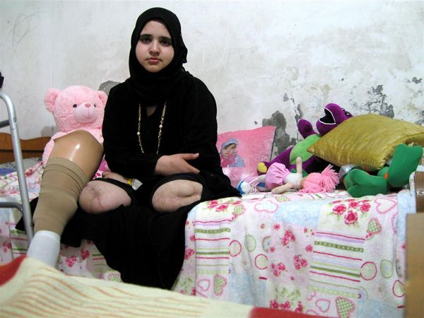 Jamila (age 15) sits at home in Gaza City. She lost both her legs, and her sister, Shaza, was killed during the December 2008-January 2009 Israeli military incursion. A missile hit their home as they played on the roof. The one-month conflict killed 1,300 Gazans, including 350 children.    Jamila's photograph was taken by Rana, 18, during a UNICEF-organized children's photography workshop. - 2009 © UNICEF/Rana Matar - http://www.unicef.org/photography