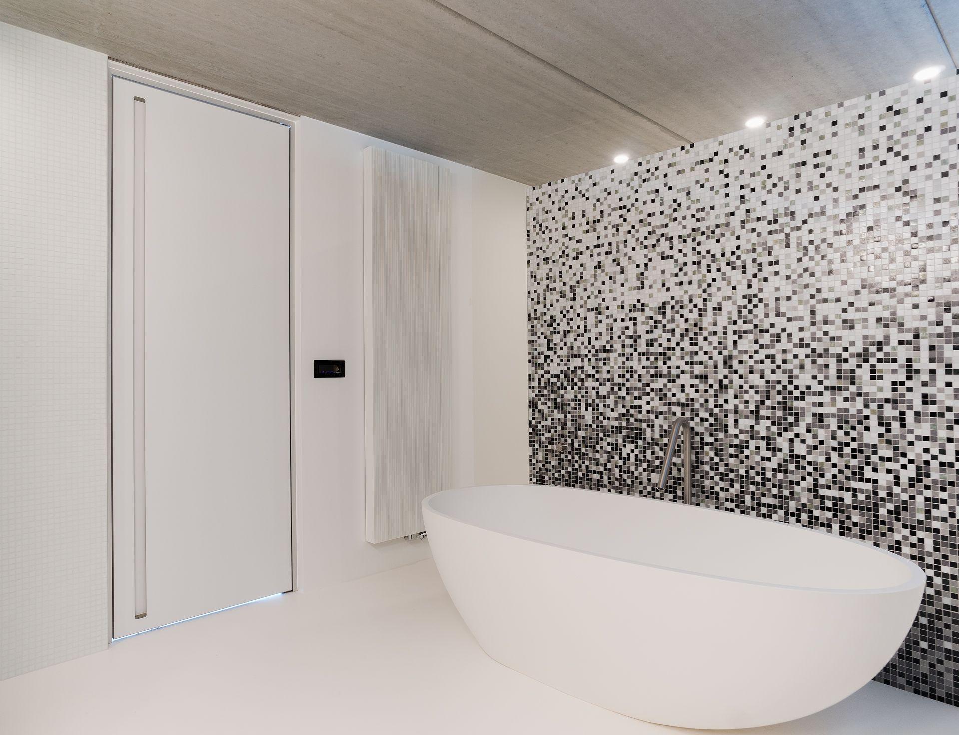 Moderne badkamer met wit bad, witte gietvloer en zwart/wit mozaïek ...