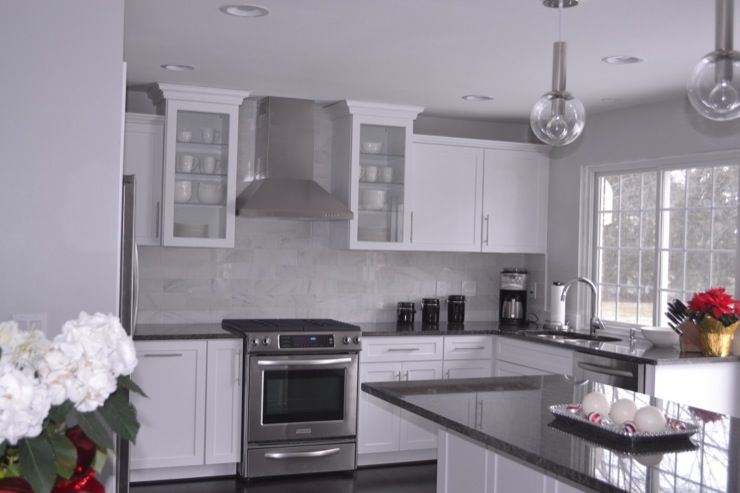 Steel Gray Granite Countertops, Carrara Marble Backsplash, White Cabinets,  And Stainless Steel Appliances.