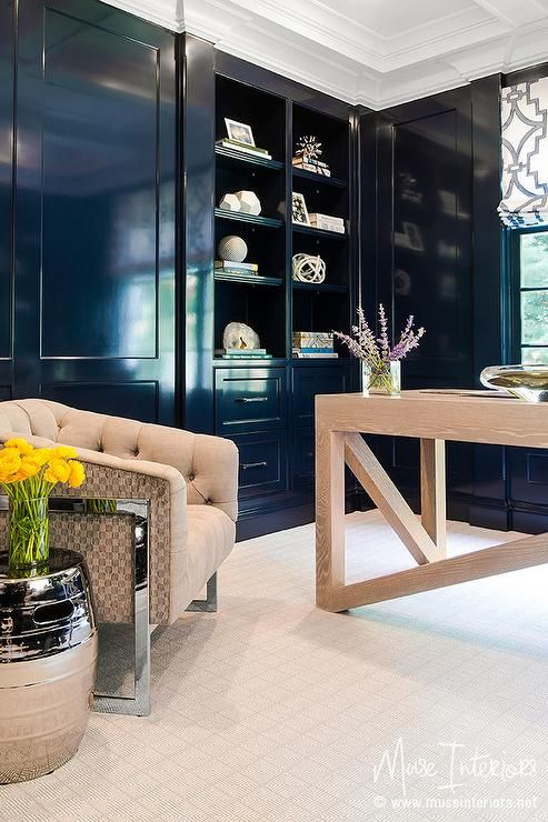 Navy paneled office boasts a tufted linen chair and a