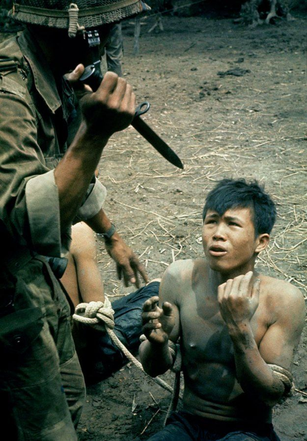 """Caption from LIFE. """"A captured Viet Cong kneels in terror as Vietnamese guard threatens him with bayonet. The guard demanded to know where arms were hidden. No reply. The guard let him go to a prison camp unharmed. In interrogating prisoners each side in the Vietnam war occasionally resorts to terror."""" (Larry Burrows—Time & Life Pictures/Getty Images) See more: http://ti.me/Ot15KH"""