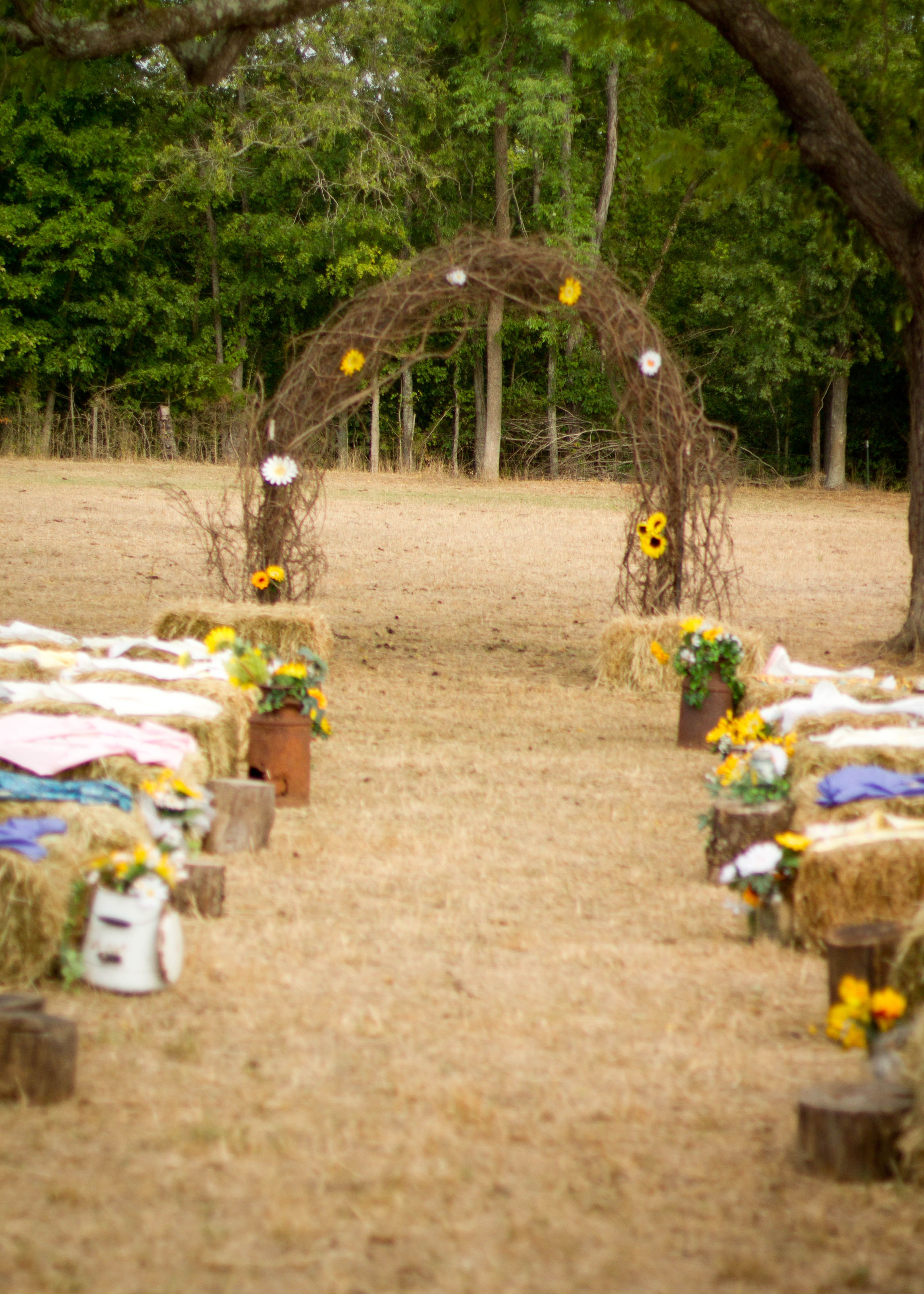 Rustic Wedding Arch Made Out Of Grapevine Seating Was Hay Bales With Material On Them