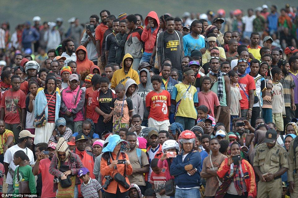 Papuanese people along with tourists watch the 27th annual Baliem Valley Festival in Walesi district in Wamena, Papua Province