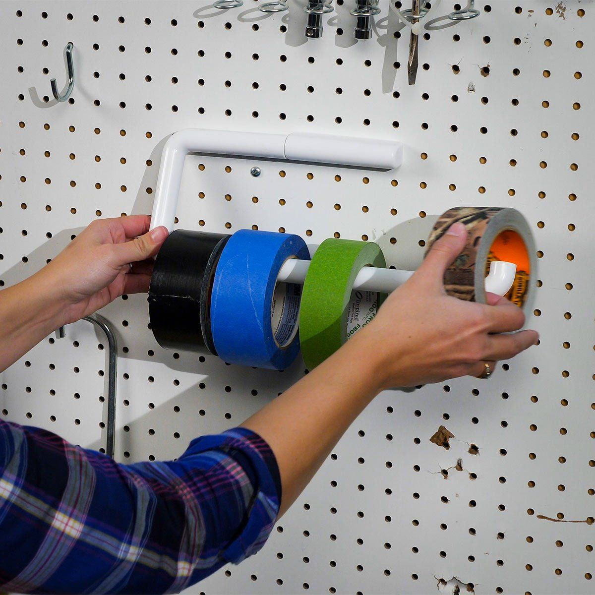 Rather than take up space in a drawer or cabinet for storing rolls of tape, mount an old paper towel dispenser to your wall or pegboard. It can hold several rolls of duct tape, painter's tape, etc., within easy reach. #familyhandymanstuff