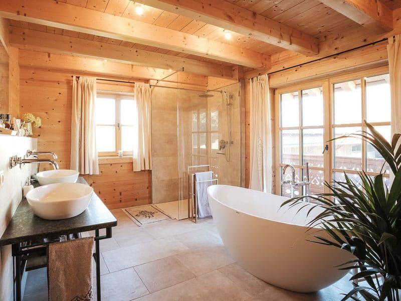 Die Freistehende Badewanne Ist Der Blickfang Im Holzernen Badezimmer Foto Chiemgauer Holzhaus Holzhaus Badezimmer Rustikal Haus
