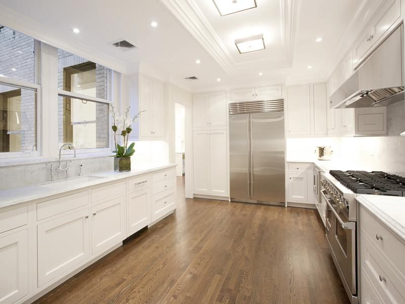 new york city apartment kitchen white cabinets hardwood wood floors white carara marble countertops stainless