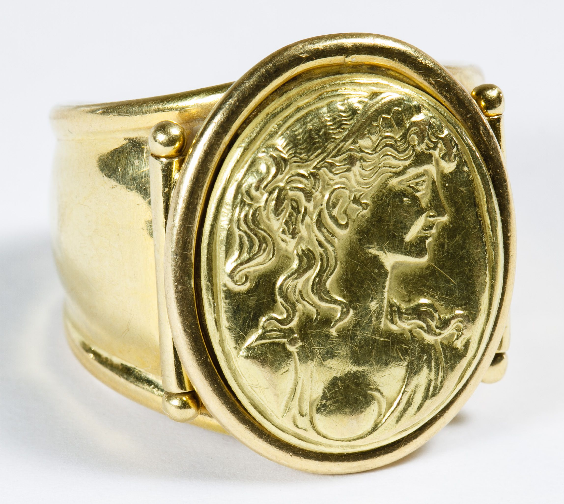 Lot 121: 18k Gold and Embossed Cameo Ring; Having an cameo embossed panel attached to an open back ring; marked 750 inside band