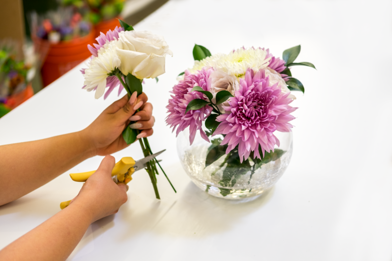 """In this arrangement The Bouqs Co. used purple dahlias for the larger blooms, white button poms and 'Early Gray' roses—which have a really unique, gorgeous color that we are absolutely loving, especially looking ahead to fall/winter—for the smaller blooms, and ruscus for the greenery,"""""""