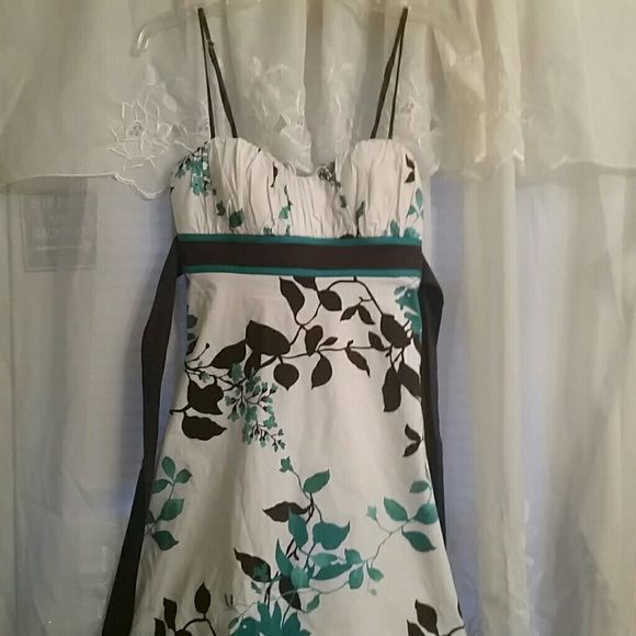 BEAUTIFUL BOUTIQUE DRESS! This dress is absolutely gorgeous! Only worn once, I purchased this at a local well known boutique. It is in absolute mint condition. White with turquoise and dark chocolate with extremely fancy detail at the bottom, this is an extremely beautiful dress and is very very flattering for any lady! SPEECHLESS  Dresses