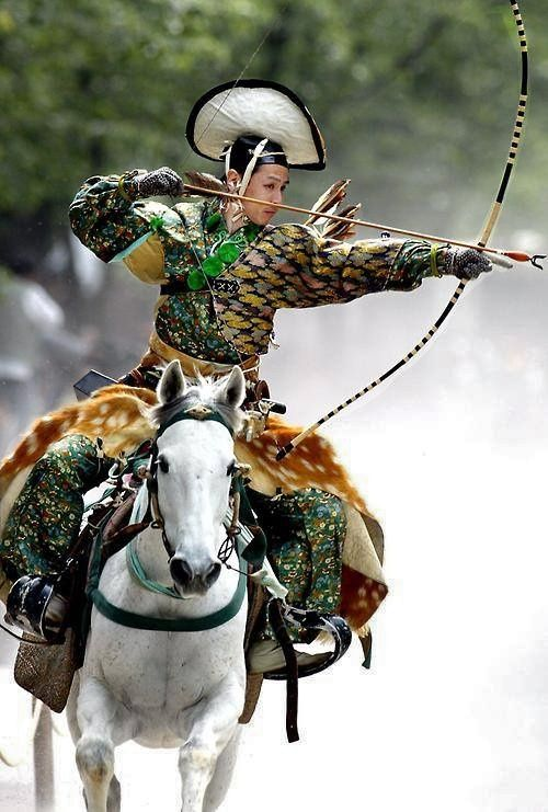 An archer dressed in traditional samurai garb displays Yabusame (archery while on horseback).  Japan.