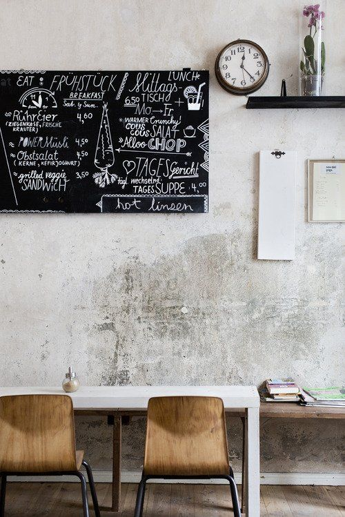 cement walls, chalk board, wooden chairs