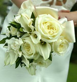 Wedding Bouquet Arranged With: White Roses, White Calla Lilies, White Gardenias, Green Foliage Hand Tied With An Ivory Satin Ribbon