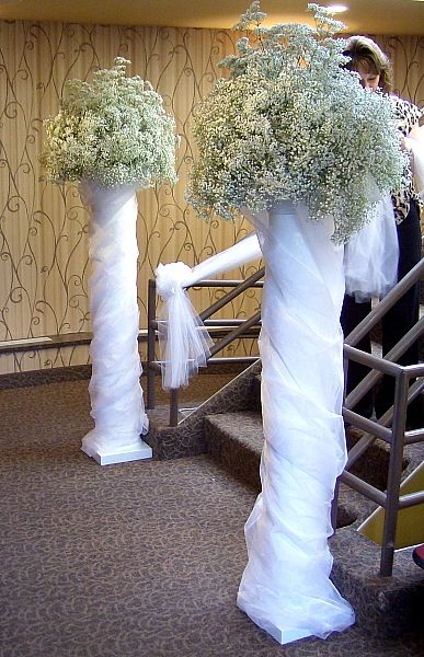 Our columns placed at the base of a staircase decorated with organza swags and Babies Breath spheres.