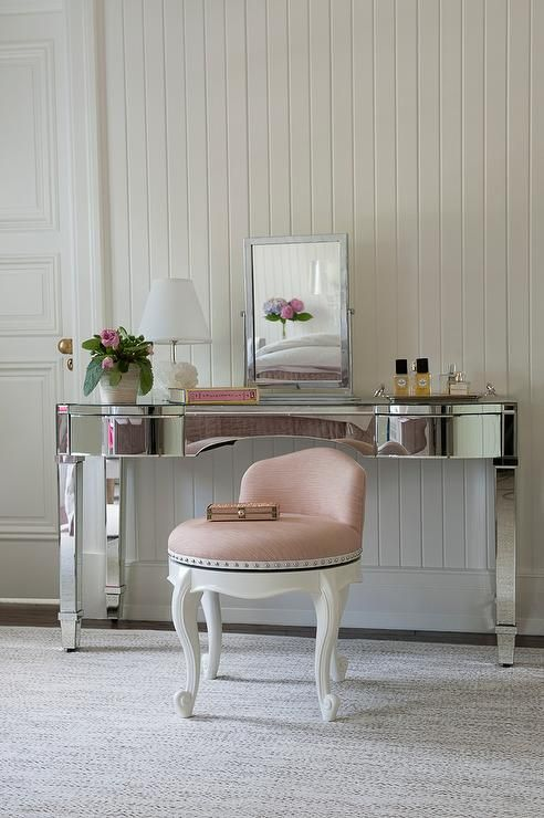 Chic Dressing Room Boasts A Mirrored Make Up Vanity Paired With Blush Pink Stool Atop White And Gray Rug