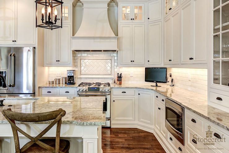Traditional kitchen features ivory cabinetry accented with oil ...