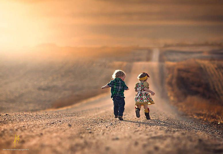 As crianças correndo por uma estrada deserta dos Estados Unidos