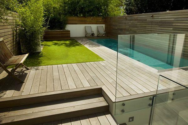 Beton Holz Feuerstelle Pergola Kies Bodenbelag Sitzkissen Swimming