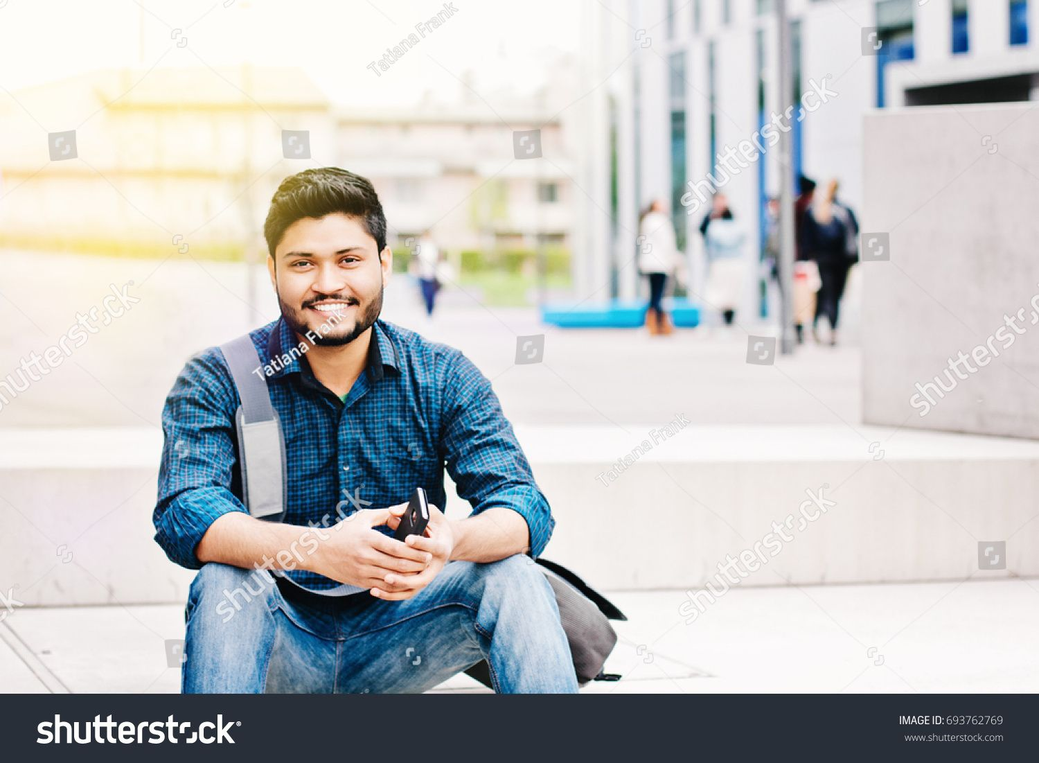 Happy indian male student holding smartphone sitting