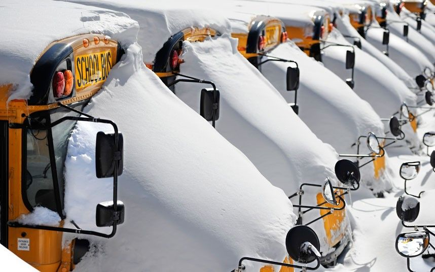 School buses are covered in snow after a winter storm in