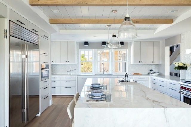 All-white kitchen with exposed wooden beams and a marble island