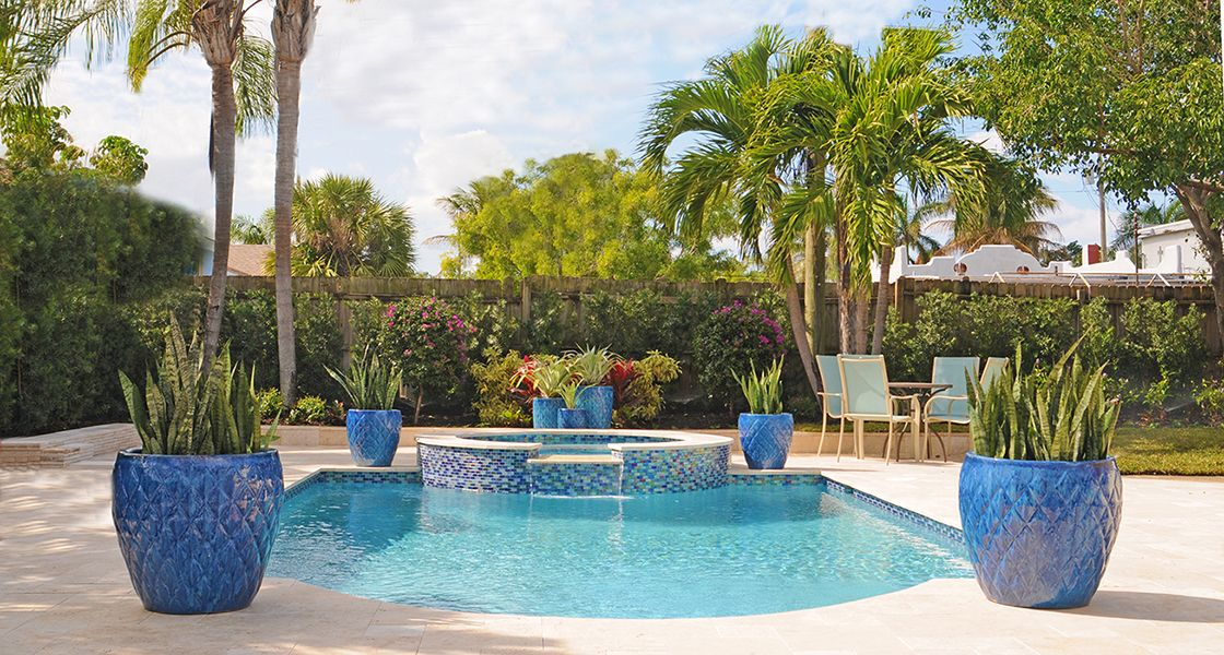 Blue Pots Grace A Tropical Pool Designed By Pamela Crawford Learn Her Secrets In Her Pool Landscape Design Backyard Pool Landscaping Tropical Pool Landscaping