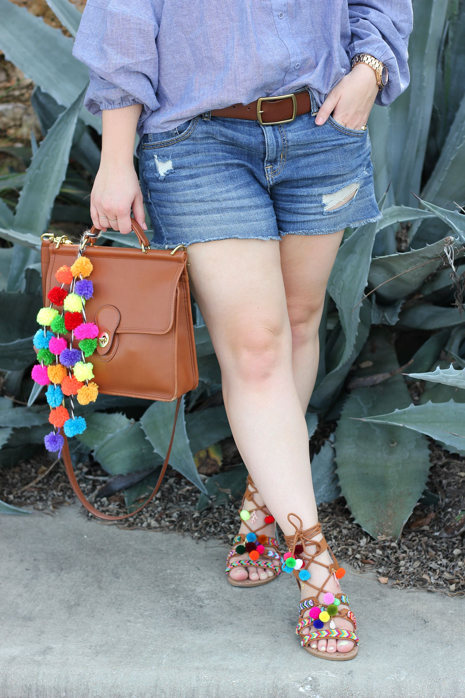 Dress up a pair of plain tan sandals with colorful pompoms and embroidery thread for a festive summer DIY!
