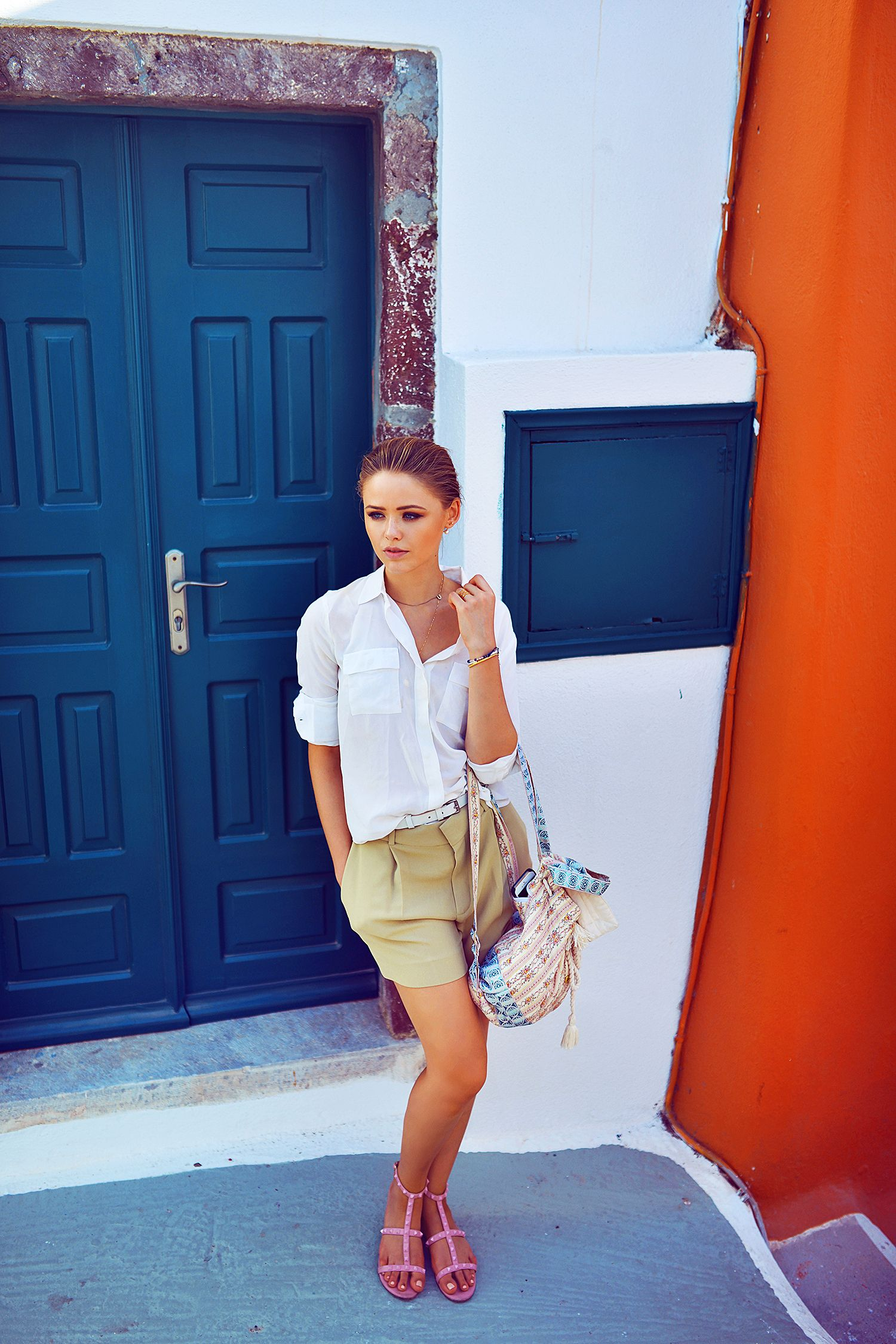 Kristina Bazan is wearing short shorts from Chloé, white top from Anine Bing and shoes from Valentino