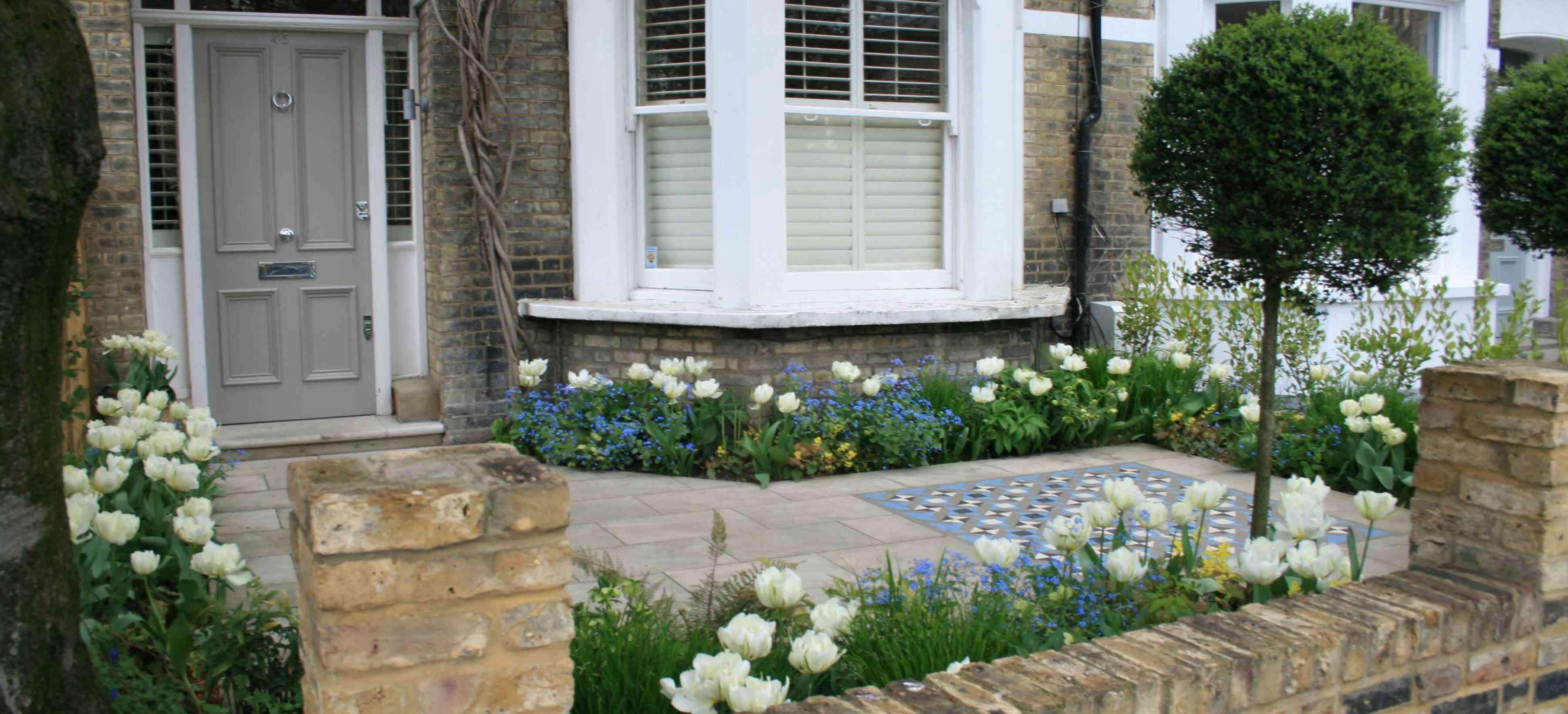 Neutral Grey Front Door With Sidelights Transom White Trim Tan Brick Walls Landscaping Front Garden Design Front Garden Townhouse Garden