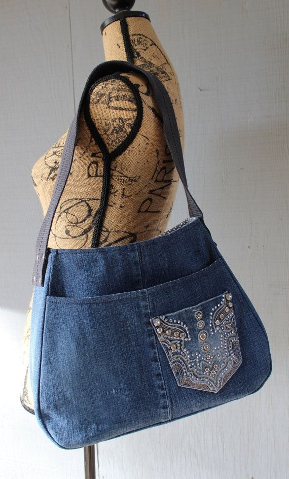 This is a handbag is handmade from upcycled denim jeans and lined with a soft cotton gray and white polka dot printed fabric with a large front pocket, two interior pockets, back zipper pocket and an added pocket sewn on the from for an added touch. The strap is created from an upcycled cotton webbing belt with four rivets hammered on each side to reinforce the strap. This handbag is lined with a dense interfacing throughout the bag for sturdiness. Dimensions: 13W(bottom Base), 9W (top) x…