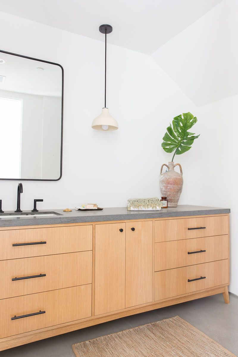 In this modern bathroom theres a large wood vanity with a concrete countertop and black hardware bathroomdesign woodandconcrete