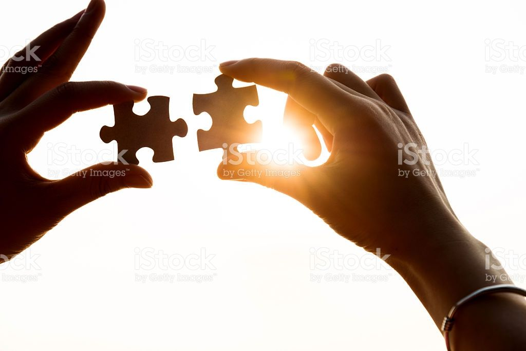 human hands connecting jigsaw puzzle pieces teamwork concept