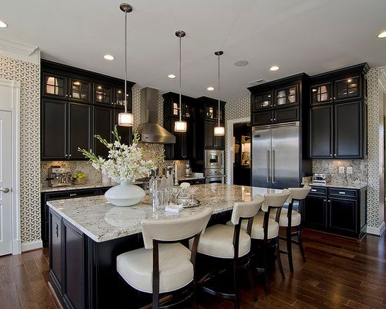 Traditional kitchen with dark (black?) cabinets, white countertop, and large island.