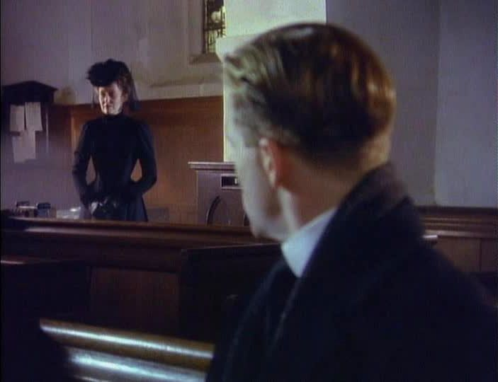 The Woman in Black standing at the back of the church during