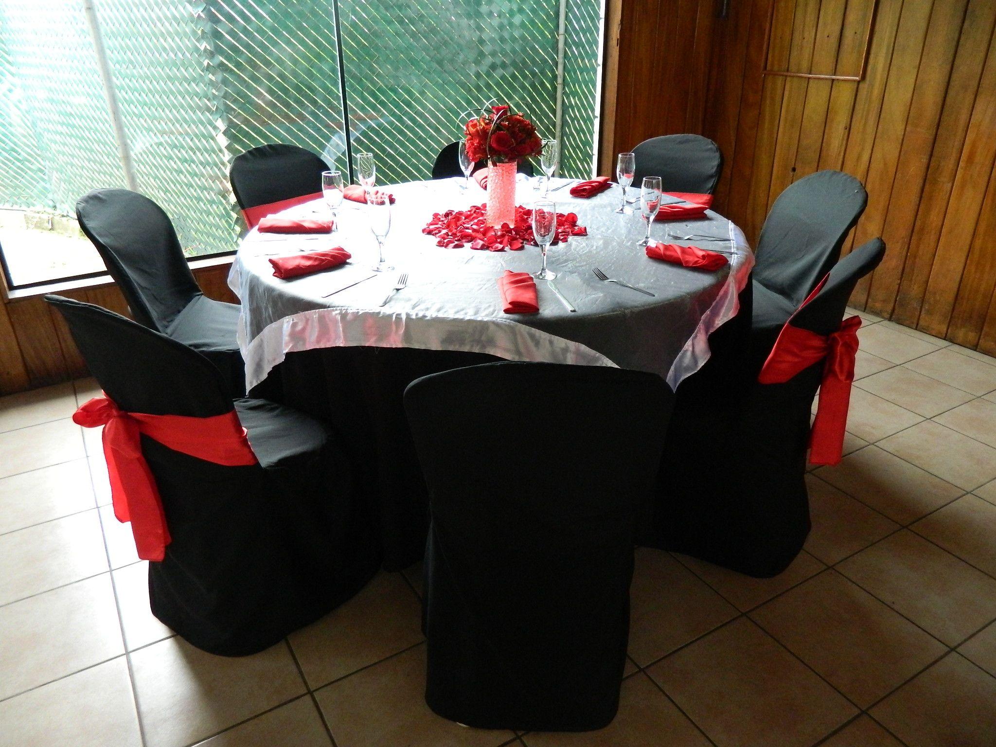 montaje con mantel negro cubre mantel plateado combinado con rojos lo que le da