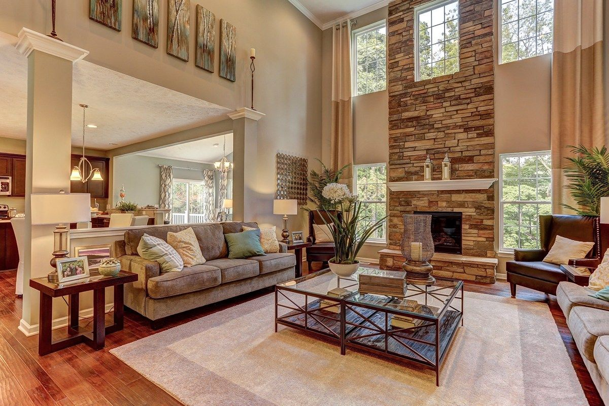Windows flank a soaring stone fireplace in this two story for Great living room ideas