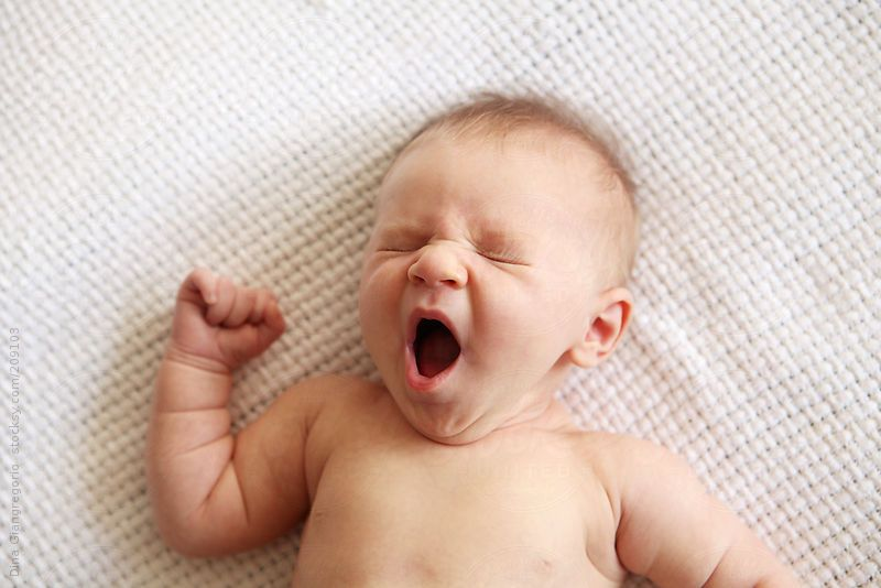 Multiethnic fair skinned newborn baby yawning by Dina Giangregorio #stocksy #realstock