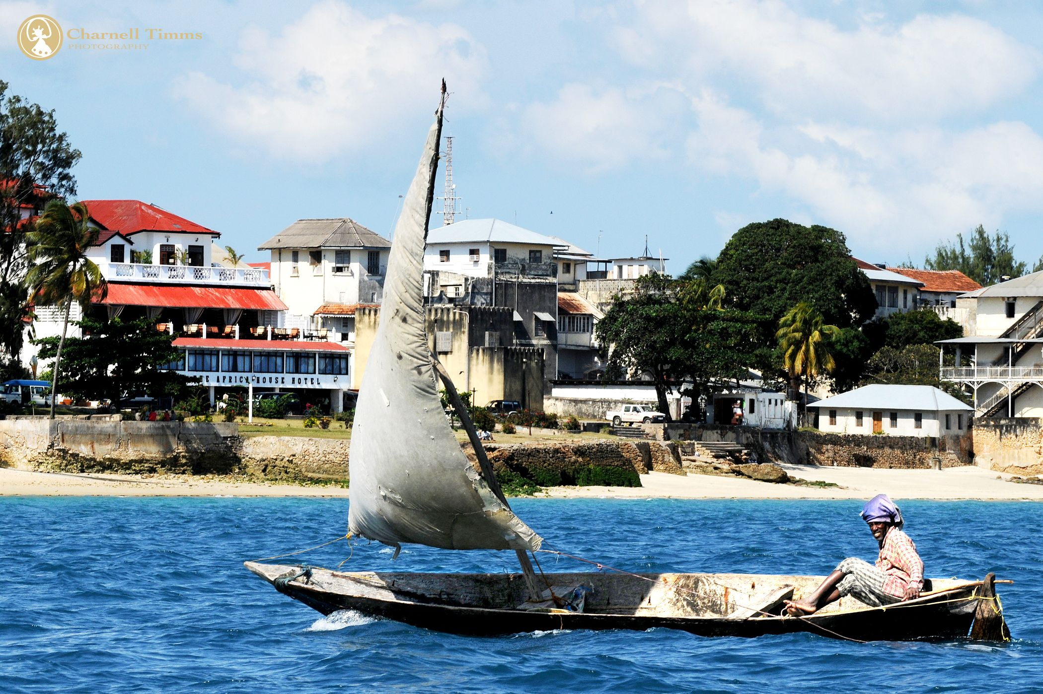 Dhow sailor in Stone Town with the iconic African House Hotel in the background. Charnell Timms Photography