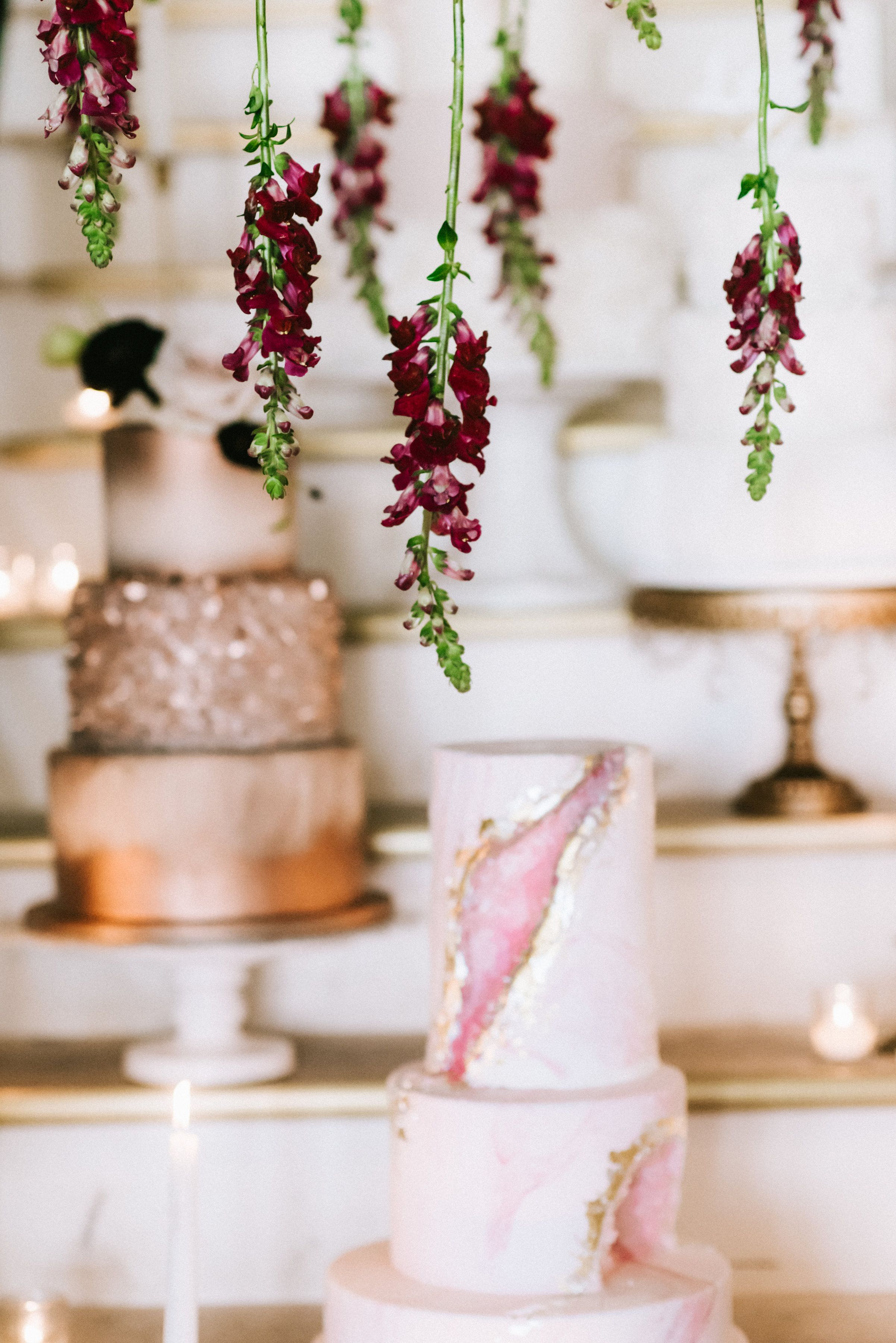 Floral Design by Color Theory Collective | Photo by Sarah Goss | Planning and Styling by Eighteenth Avenue Events | Cakes by Cakes ROCK ATX | Hanging flowers above wedding cakes | Burgundy Snap Dragons Hanging as Floral Installation   Venue : One Eleven East, Hutto