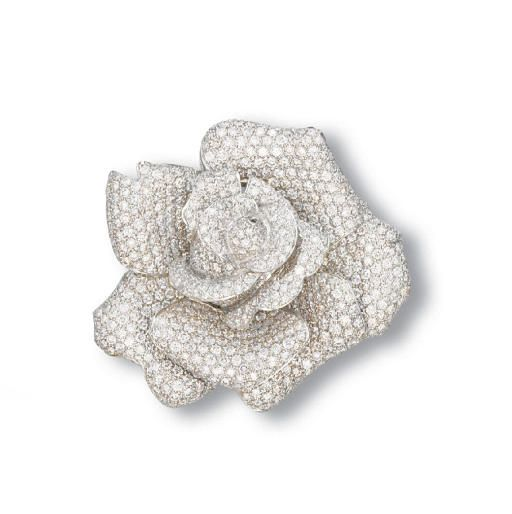 A DIAMOND ROSE CLIP BROOCH  Designed as a pavé-set diamond blooming rose, mounted in 18k white gold, (with pendant hoop for suspension), 6 cm wide.Price Realized   $19,369 Estimate $12,267 - $15,495