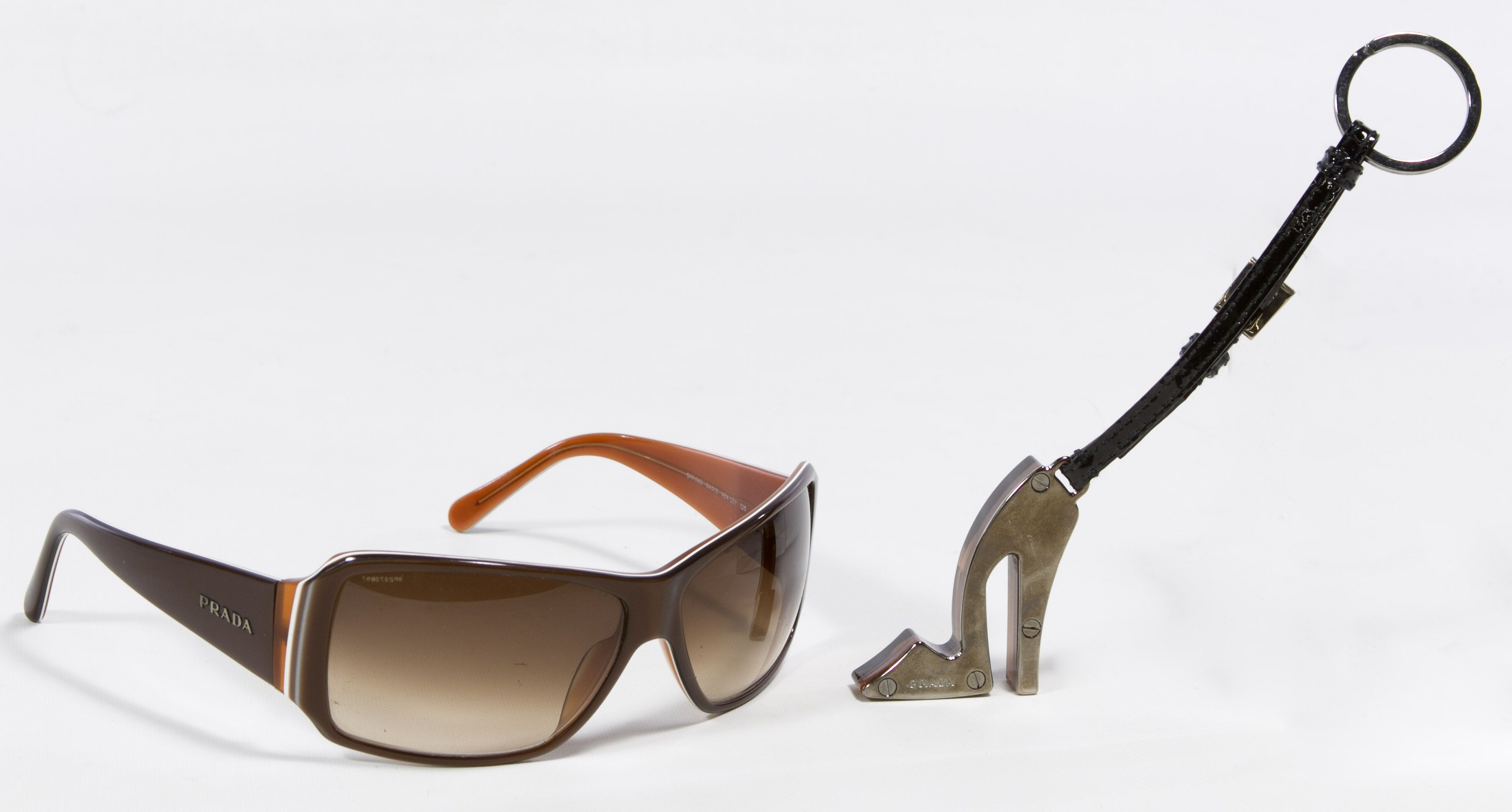 Lot 497: Prada Sunglasses and Keychain; Together with a black case and black cloth