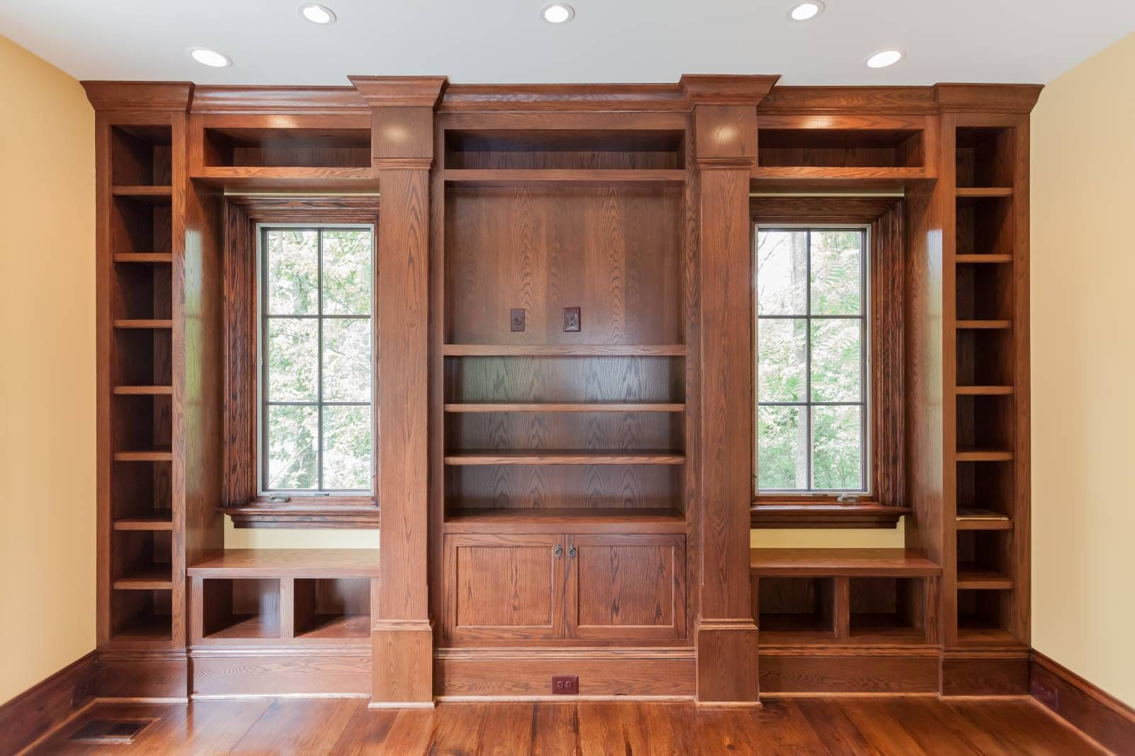 Stained wood custom built in with window seats, bookcases ...