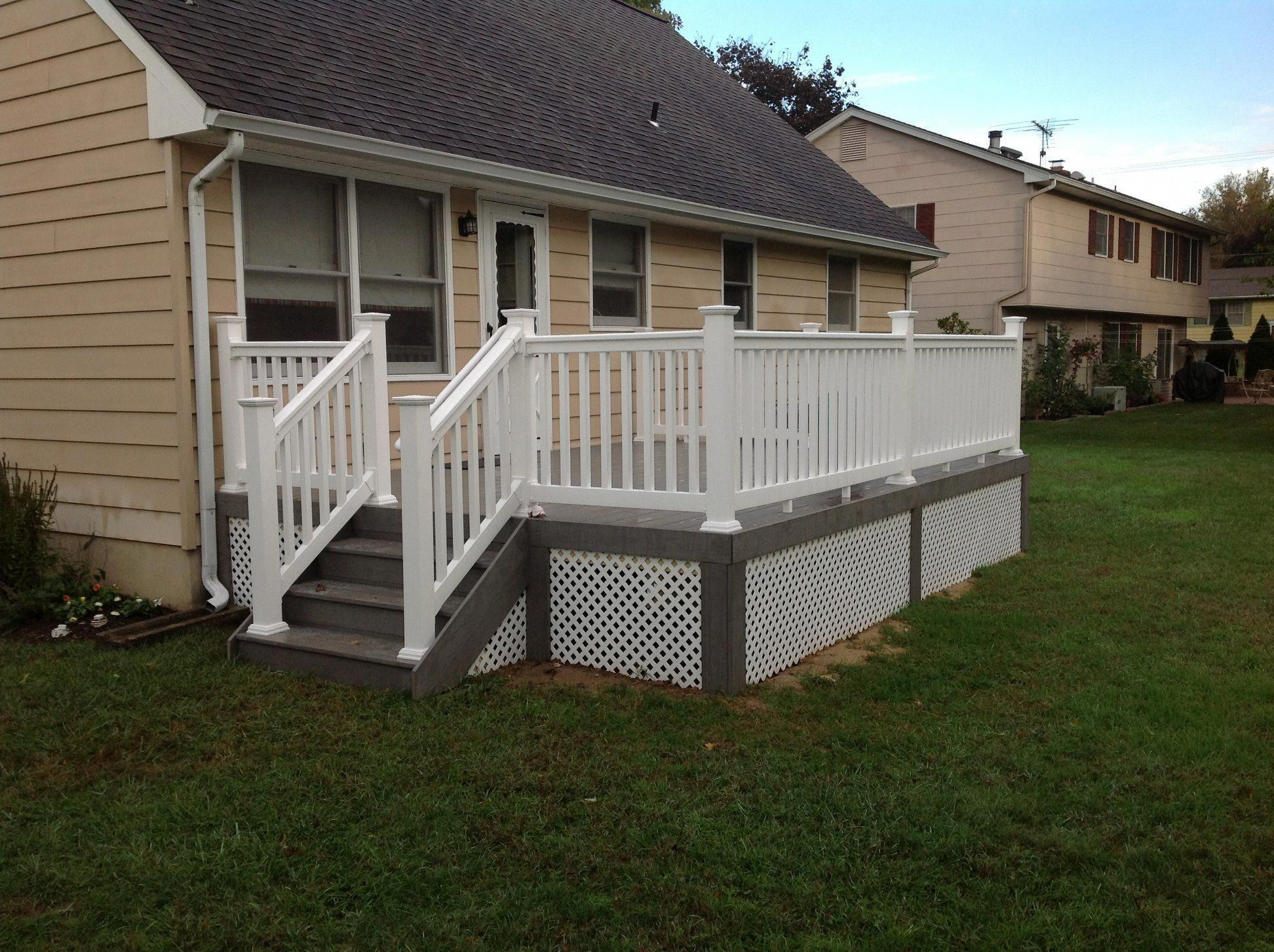 12 X16 First Story Trex Deck With White Vinyl Railing System And One Set Of Steps Leading To Ground Level Installed On Yo Building A Deck Diy Deck Deck Design