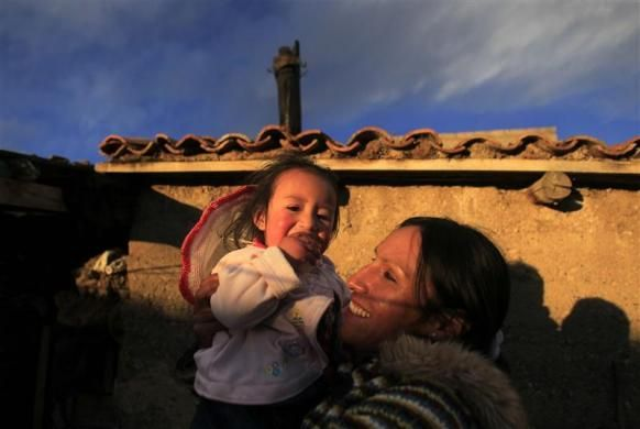 Marathon runner Gladys Tejeda, the first Peruvian athlete who qualified for the 2012 London Olympic Games, holds her niece Ariana at her home in the Andean province of Junin, May 13, 2012.  REUTERS/Pilar Olivares