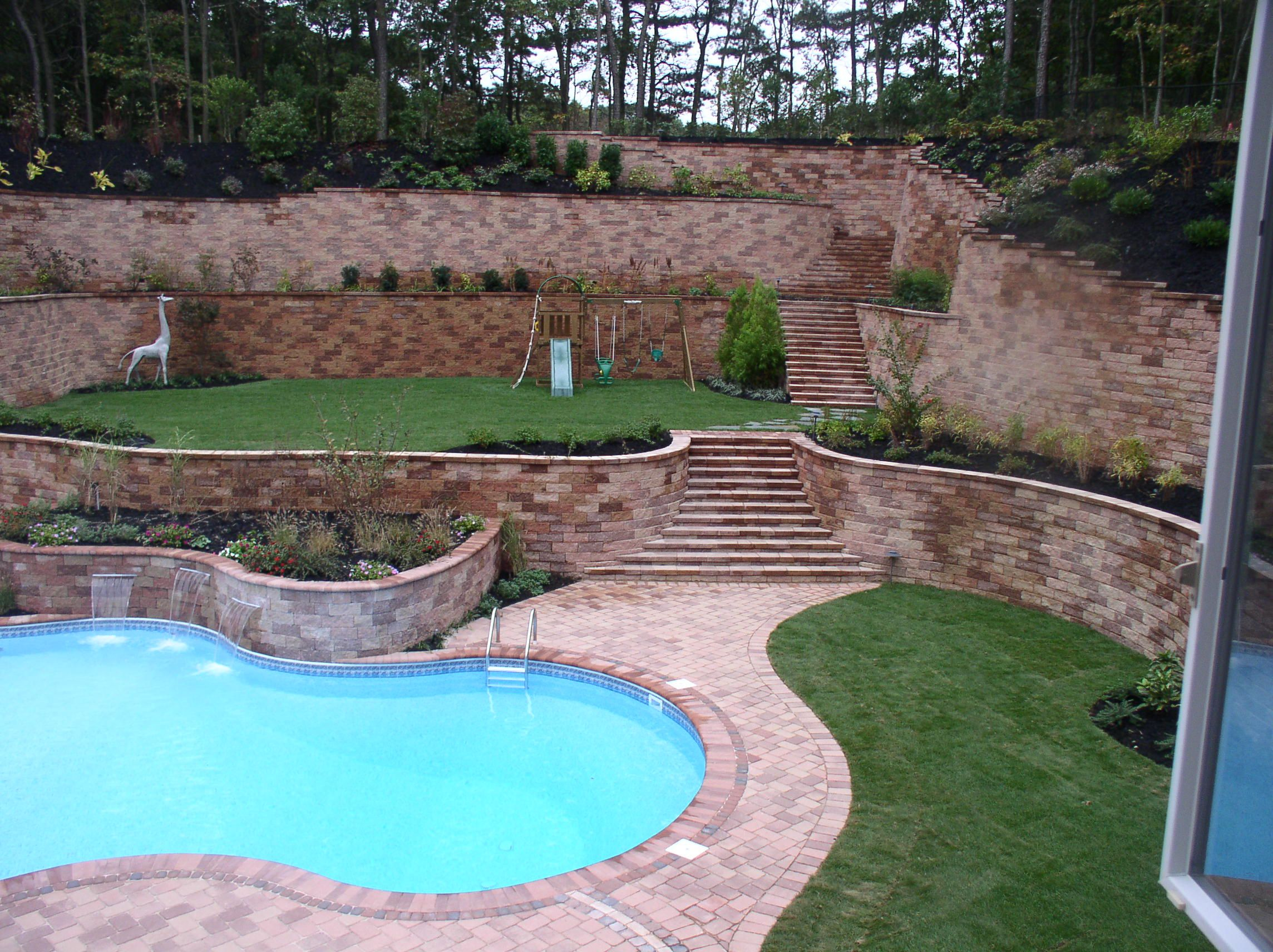 Large Back Yard Landscaping With Retaining Wall Custom Retaining Walls Garden Walls Seat Wall Backyard Landscaping Designs Sloped Backyard Pool Landscaping