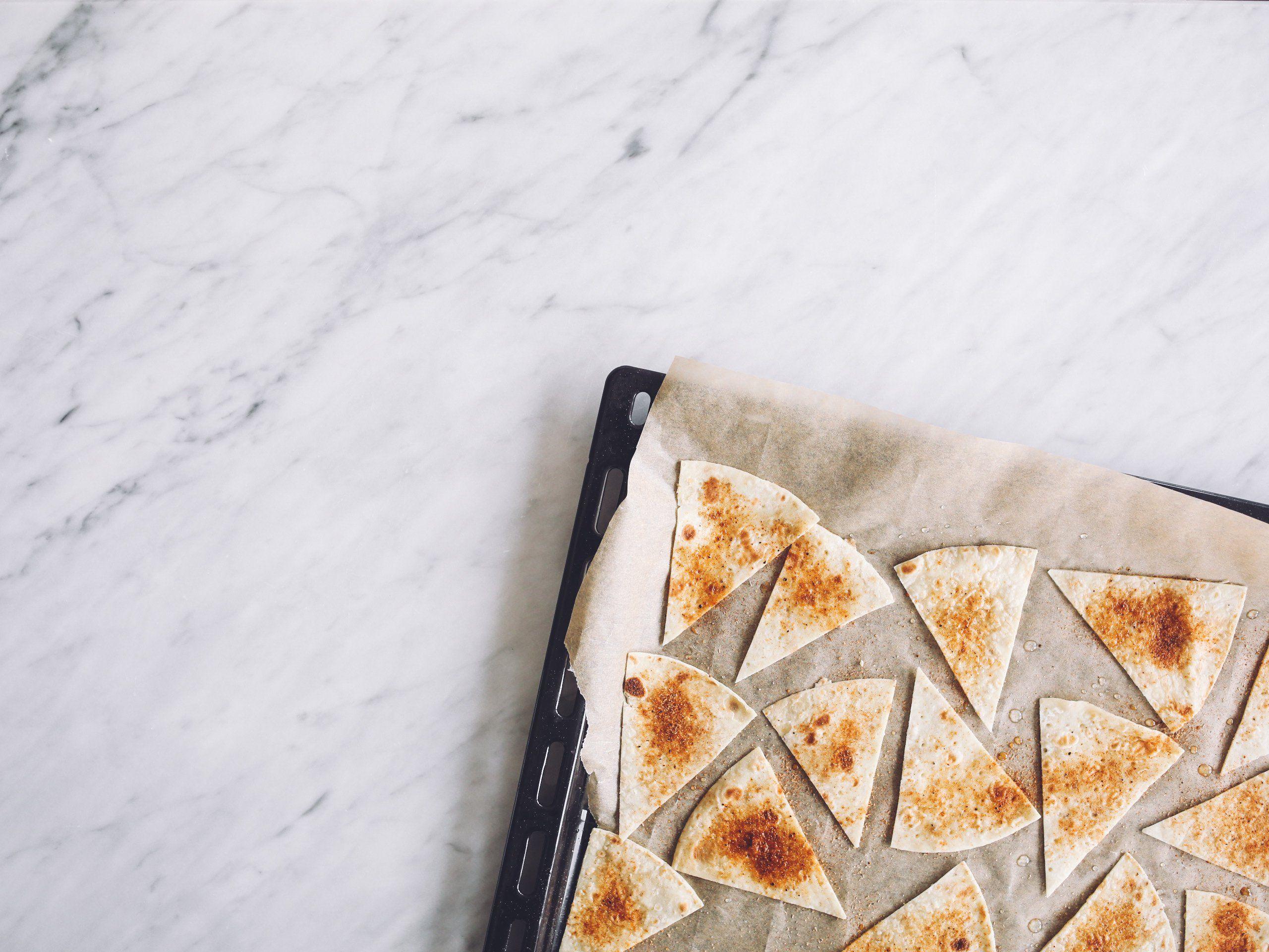 Kjøp en pakke med speltlomper. Skjær dem opp mens de ligger oppå hverandre som om det skulle vært en pizza, og plasser deretter «slicene» over på et bakepapir. Pensle dem med litt vann og strø favorittkrydderet ditt over! Jeg brukte grillkrydder, paprikakrydder og chilikrydder. Det synes jeg er en helt fantastisk god kombinasjon! Sett brettet inn i ovnen på 180°C å la chipsen steke til den blir skikkelig crunchy og får en gyllen og fin farge. Det tar ca. 5-7 minutter!