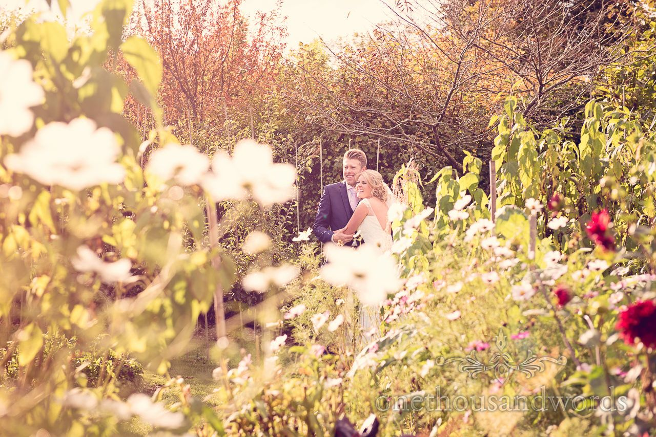 Newlyweds in garden at Holme for Gardens Dorset wedding Photography by one thousand words wedding photographers