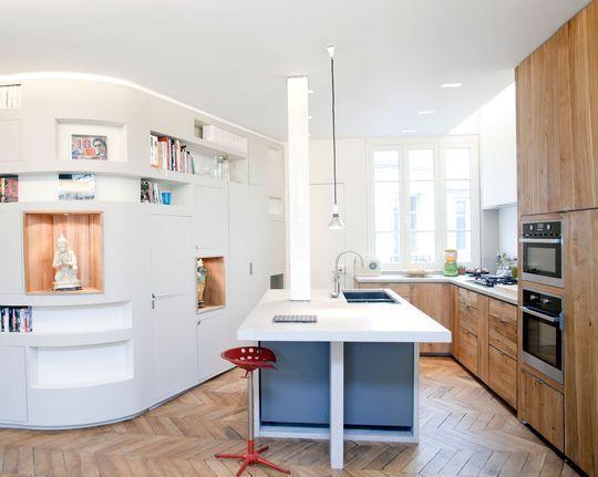 Une cuisine ouverte qui mixe les matériaux dans un appartement